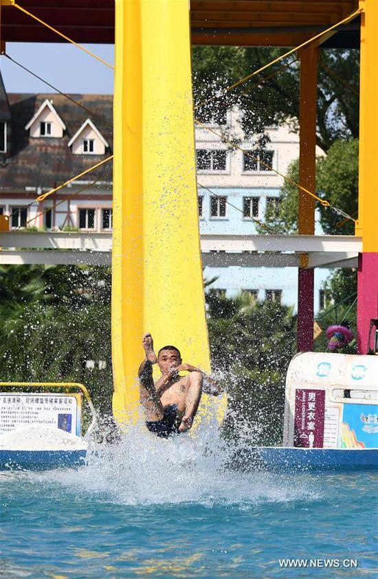 Tourists played in water to keep cool in a water park in Chongqing, July 11, 2017. An orange level high temperature warning is issued by the meteorological observatory of southwest China's Chongqing Municipality Tuesday. (Xinhua/Wang Quanchao)
