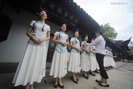 Tour guides bite chopsticks to improve their etiquette at the Slender West Lake scenic spot in Yangzhou, east China's Jiangsu Province, July 12, 2017. Wednesday marks the first day of the dog days, which means the three periods of the hottest season each year. Tour guides here practised their deportment even in the intense heat of summer. (Xinhua/Meng Delong)