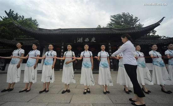 Tour guides practise their welcome gestures at the Slender West Lake scenic spot in Yangzhou, east China's Jiangsu Province, July 12, 2017. Wednesday marks the first day of the dog days, which means the three periods of the hottest season each year. Tour guides here practised their deportment even in the intense heat of summer. (Xinhua/Meng Delong)