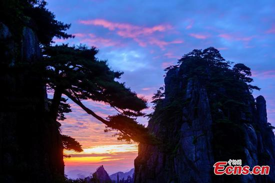 A spectacular sunrise at Huangshan Mountain in East China's Anhui Province, July 12, 2017. The mountain, a UNESCO World Heritage Site, is well known for its scenery, sunsets, pine trees, and views of clouds from above. (Photo: China News Service/Fang Lihua)