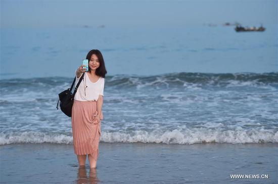 A woman takes selfie at the Jinluanwan Bay of Dongshan County in southeast China's Fujian Province July 13, 2017. Summer heat has driven people to the seaside to enjoy the coolness in Dongshan County. (Xinhua/Song Weiwei)