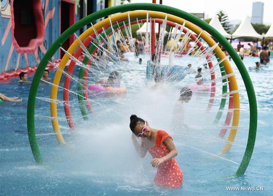 A girl plays in a water park in Chongqing, southwest China, July 16, 2017. An orange level high temperature warning is issued by the local meteorological observatory on Sunday. (Xinhua/Wang Quanchao)