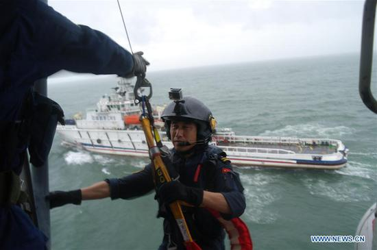 Rescuers transfer trapped tourists from Nanpeng Island, some 35 km east of Zhapo, Yangjiang City, south China's Guangdong Province, July 16, 2017. A total of 49 tourists who had been stranded on Nanpeng Island in the South China Sea were picked up and moved to safety on Sunday morning, authorities said. (Xinhua)