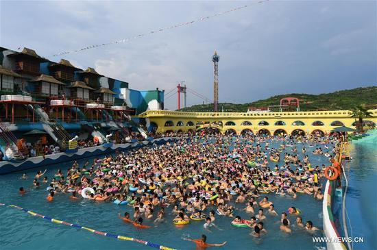 People play in a water park in Chongqing, southwest China, July 16, 2017. An orange level high temperature warning is issued by the local meteorological observatory on Sunday. (Xinhua/Wang Quanchao)