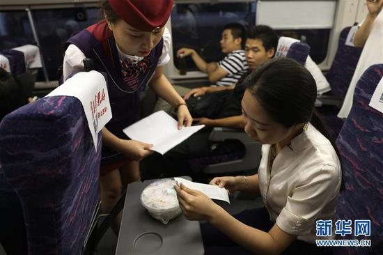 A passenger receives her food from an attendant. (Photo/Xinhua)
