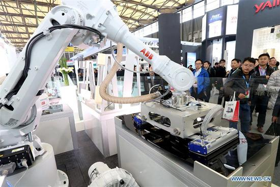 Visitors watch a robot during the Appliance & Electronics World Expo 2017 in east China's Shanghai, March 9, 2017. China's gross domestic product expanded 6.9 percent year on year in the first half of the year to about 38.15 trillion yuan (5.62 trillion U.S. dollars), data from the National Bureau of Statistics (NBS) showed Monday. (Xinhua/Chen Fei)