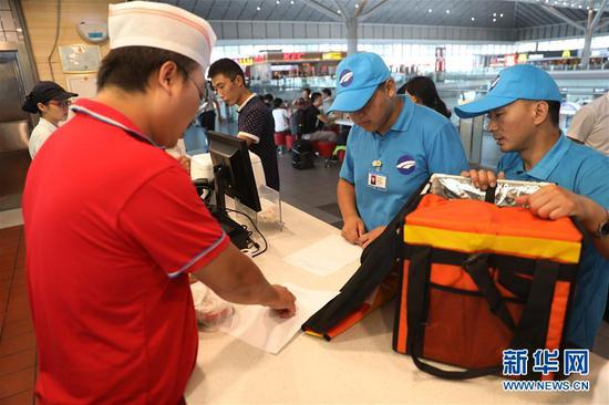 Deliverymen put food into the warm box at a restaurant. (Photo/Xinhua)