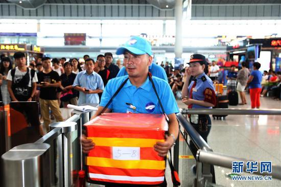A food deliveryman on his way to deliver meals to passengers on a bullet train in Xi'an North Railway Station in Xi'an, Shaanxi province, July 17, 2017. Passengers on some bullet trains are allowed to order meal online from restaurants starting Monday. (Photo/Xinhua)