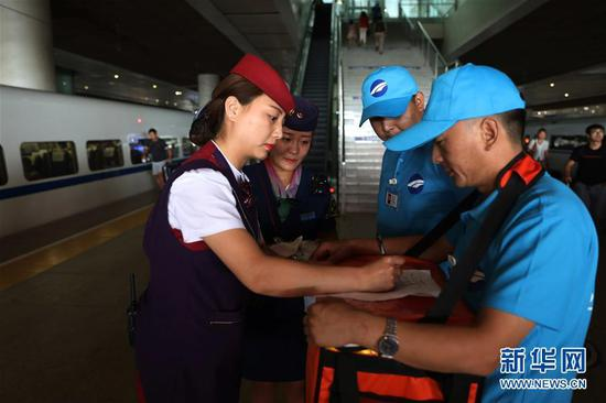 Food deliverymen hand the food to a train attendant. (Photo/Xinhua)