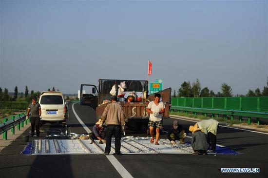 Workers do the preparation work before a section of a freeway between Beijing and northwest China's Xinjiang Uygur Autonomous Region, is put into use in Bayan Nur City, north China's Inner Mongolia Autonomous Region, July 14, 2017. The total length of the expressways in Inner Mongolia has reached 6,000 kilometers so far. (Xinhua/Deng Hua)