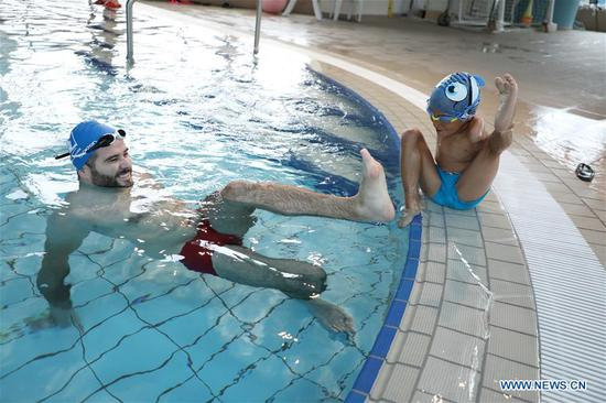 Disabled boy Ismail Zulfic (R) plays with his trainer in a swimming pool in Sarajevo, Bosnia and Herzegovina, July 25, 2017. Ismail Zulfic started to learn swimming 18 months ago. He had to go all the way from Zenica to Sarajevo (70km apart) twice a week to learn the new skill. (Xinhua/Haris Memija)
