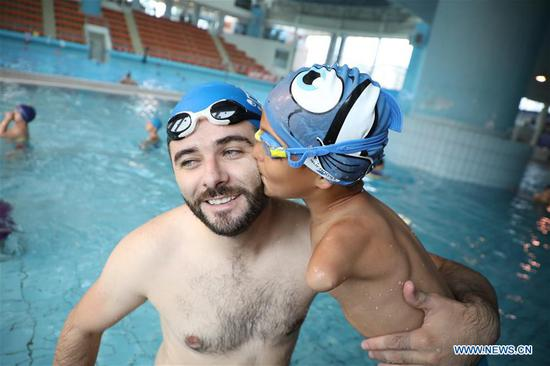 Disabled boy Ismail Zulfic (R) kisses his trainer in a swimming pool in Sarajevo, Bosnia and Herzegovina, July 25, 2017. Ismail Zulfic started to learn swimming 18 months ago. He had to go all the way from Zenica to Sarajevo (70km apart) twice a week to learn the new skill. (Xinhua/Haris Memija)