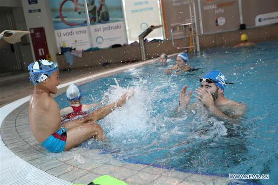 Disabled boy Ismail Zulfic (L) plays with his trainer in a swimming pool in Sarajevo, Bosnia and Herzegovina, July 25, 2017. Ismail Zulfic started to learn swimming 18 months ago. He had to go all the way from Zenica to Sarajevo (70km apart) twice a week to learn the new skill. (Xinhua/Haris Memija)