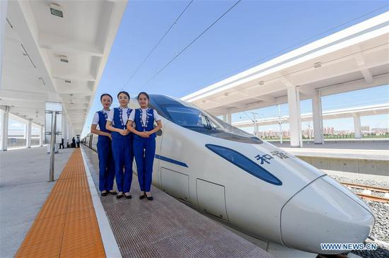 Crew members pose for a photo with the bullet train at Ulanqab Railway Station in Ulanqab, north China's Inner Mongolia Autonomous Region, Aug. 3, 2017. The first high speed railway in Inner Mongolia Autonomous Region linking Hohhot and Ulanqab started operation on Thursday. The 126-kilometer-long railway is part of the high-speed railway that links Hohhot to Zhangjiakou in Hebei Province, the co-host city of the 2022 Olympic Winter Games. And the travel time between Ulanqab and Hohhot will be shortened to 40 minutes. (Xinhua/Lian Zhen)
