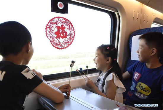 Passengers enjoy natural scenery on a train of Zhangjiakou-Hohhot high speed railway in north China's Inner Mongolia Autonomous Region, Aug. 3, 2017. The first high speed railway in Inner Mongolia Autonomous Region linking Hohhot and Ulanqab started operation on Thursday. The 126-kilometer-long railway is part of the high-speed railway that links Hohhot to Zhangjiakou in Hebei Province, the co-host city of the 2022 Olympic Winter Games. And the travel time between Ulanqab and Hohhot will be shortened to 40 minutes. (Xinhua/Wang Zheng)