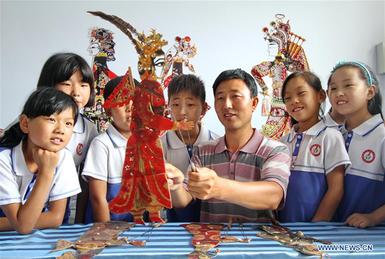 Shadow play artist Zhang Yingfeng explains knowledge of shadow play for left-behind children, in Handan City, north China's Hebei Province, July 26, 2017. Shadow play is China's intangible cultural heritage. The Jiudian Primary School of Feixiang District in Handan City started a shadow play lesson for free, which enriches the summer vacation life of kids. (Xinhua/Mu Yu)