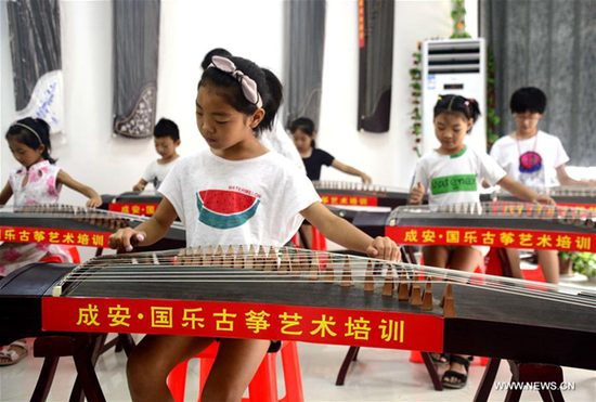 Kids learn playing guzheng, a traditional Chinese music instrument, in Cheng'an County of north China's Hebei Province, July 26, 2017. A series of summer vacation activities are held in Cheng'an, offering traditional culture courses on guzheng, erhu and allegro skills. (Xinhua/Wang Xiao)