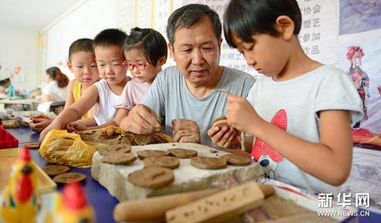 Children experience doing clay sculptures under the guidance of clay artists in the Cultural Center of Raoyang County, north China's Hebei Province, Aug 14, 2017. (Xinhua/Zhu Xudong)