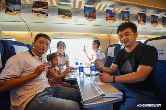 Passengers show their tickets on the bullet train from Hohhot to Ulanqab, north China's Inner Mongolia Autonomous Region, Aug. 3, 2017. The first high speed railway in Inner Mongolia Autonomous Region linking Hohhot and Ulanqab started operation on Thursday. The 126-kilometer-long railway is part of the high-speed railway that links Hohhot to Zhangjiakou in Hebei Province, the co-host city of the 2022 Olympic Winter Games. And the travel time between Ulanqab and Hohhot will be shortened to 40 minutes. (Xinhua/Lian Zhen)