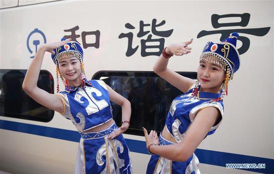 Performers pose for a photo with the bullet train at Ulanqab Railway Station in Ulanqab, north China's Inner Mongolia Autonomous Region, Aug. 3, 2017. The first high speed railway in Inner Mongolia Autonomous Region linking Hohhot and Ulanqab started operation on Thursday. The 126-kilometer-long railway is part of the high-speed railway that links Hohhot to Zhangjiakou in Hebei Province, the co-host city of the 2022 Olympic Winter Games. And the travel time between Ulanqab and Hohhot will be shortened to 40 minutes. (Xinhua/Zheng Huansong)