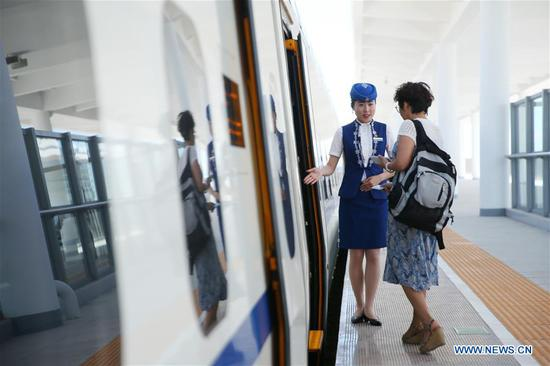 A crew member welcomes passengers at Ulanqab Railway Station in Ulanqab, north China's Inner Mongolia Autonomous Region, Aug. 3, 2017. The first high speed railway in Inner Mongolia Autonomous Region linking Hohhot and Ulanqab started operation on Thursday. The 126-kilometer-long railway is part of the high-speed railway that links Hohhot to Zhangjiakou in Hebei Province, the co-host city of the 2022 Olympic Winter Games. And the travel time between Ulanqab and Hohhot will be shortened to 40 minutes. (Xinhua/Zheng Huansong)