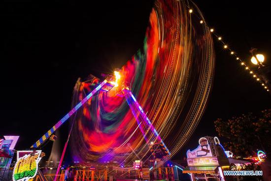 The long-exposure photo taken on Aug. 8, 2017 shows an illuminated ferris wheel at a summer carnival held on the bank of Leman Lake during the Geneva Festival in Geneva, Switzerland. (Xinhua/Xu Jinquan)