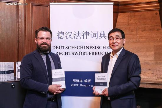 Compiler of the German-Chinese Law Dictionary Zhou Hengxiang (R) holds the dictionary during a launch ceremony at the Duncker & Humblot Publishing Company in Berlin, capital of Germany, on Aug. 8, 2017. (Xinhua/Shan Yuqi)