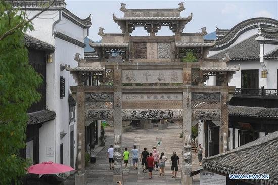 Tourists walk at a tourist site in Jiangjiazhen Town of Chun'an County, east China's Zhejiang Province, Aug. 8, 2017. Jiangjiazhen, a prosperous industrial town full of machinery plants, paper mills and iron works since the 1980s, is trying a greener development by promoting tourism and ecological agriculture in the recent years. The town is now witnessing an increasing number of tourists after the renovation of some factory buildings, construction of tourism villages and improvement of residents' house sharing service system. (Xinhua/Huang Zongzhi)