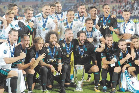 Real Madrid players celebrate with the trophy after winning the UEFA Super Cup match against Manchester United at the Philip II Arena in Skopje, Macedonia, on Tuesday. Real won 2-1. — AFP