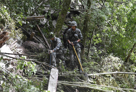 Soldiers search an area for anyone trapped after the earthquake in Jiuzhaigou County in Sichuan Province yesterday.