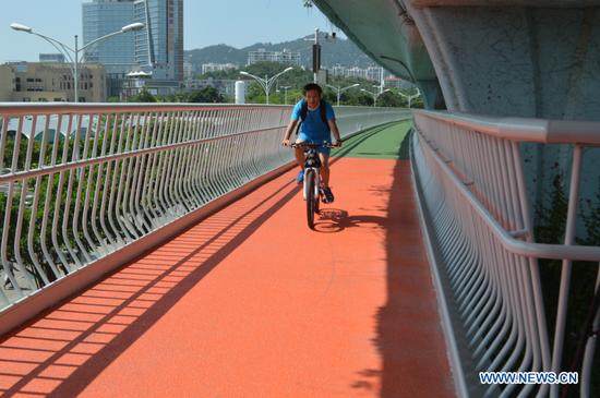 A citizen rides along an elevated bicycle path in Xiamen, southeast China's Fujian Province, Aug. 5, 2017. (Xinhuanet/Zhang Dan)