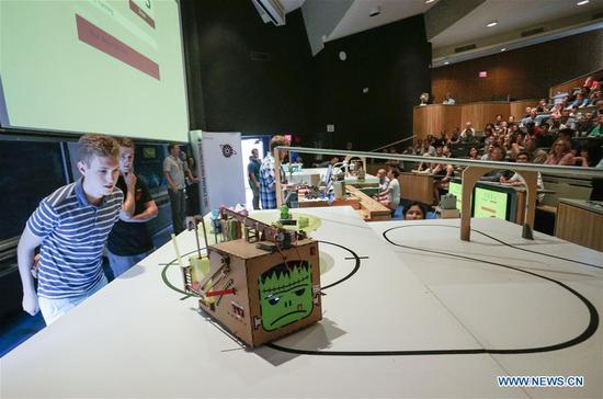 An Engineering Physics student watches his robot in action during a robot competition at the University of British Columbia (UBC) in Vancouver, Canada, Aug. 10, 2017. Sixteen student teams from UBC participated in a robot challenge to complete multiple tasks including picking up target objects and transportation in the most efficient manner. (Xinhua/Liang sen)