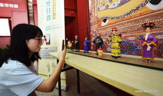 A visitor takes photos in an exhibition about Emperor Qianlong (1711-1799) at the Zhejiang Museum in Hangzhou, capital of east China's Zhejiang Province, Aug. 10, 2017. Over 200 exhibits were shown in the exhibition. (Xinhua/Long Wei)