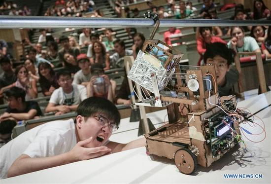 An Engineering Physics student watches a robot lifting a box during a robot competition at the University of British Columbia (UBC) in Vancouver, Canada, on Aug. 10, 2017. Sixteen student teams from UBC participated in a robot challenge to complete multiple tasks including picking up target objects and transportation in the most efficient manner. (Xinhua/Liang sen)