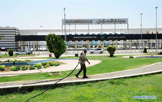 A worker waters the grass on the fairgrounds of the Damascus International Fair in Damascus, capital of Syria, on Aug. 10, 2017. After a five-year pause, the Damascus International Fair, the Syrian economy's window to the world, is returning this month. It is a sign that the country's war is declining and reviving the economy, which hit rock bottom during the prolonged conflict, has become the focus of the government. Established in 1954, the fair's last edition was held in 2011, the first year of the Syrian war. In later years, the fair was suspended because of the war before the Syrian government decided to renew it as the fair will take place on Aug. 17 this year. (Xinhua/Ammar Safarjalani)