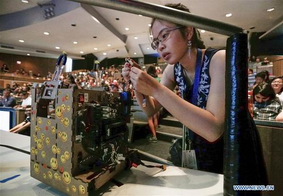 An Engineering Physics student adjusts her robot during a robot competition at the University of British Columbia (UBC) in Vancouver, Canada, Aug. 10, 2017. Sixteen student teams from UBC participated in a robot challenge to complete multiple tasks including picking up target objects and transportation in the most efficient manner. (Xinhua/Liang sen)