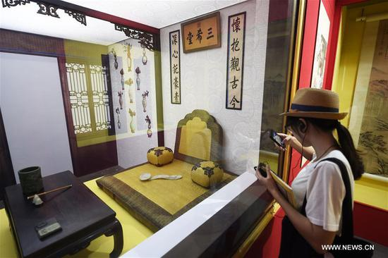 A visitor takes photos in an exhibition about Emperor Qianlong (1711-1799) at the Zhejiang Museum in Hangzhou, capital of east China's Zhejiang Province, Aug. 10, 2017. Over 200 exhibits were shown in the exhibition. (Xinhua/Li Zhong)