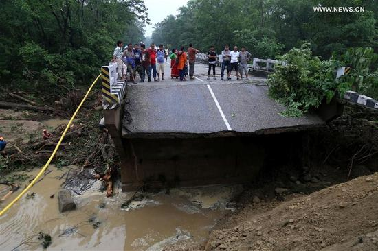 People watch the collapsed bridge caused by a flood at Gandheli river, along the East-West Highway in Nepalgunj on Aug. 13, 2017. Floods and landslides triggered by incessant rainfall since Friday have killed at least 40 people in Nepal by Sunday afternoon, according to the Ministry of Home Affairs. (Xinhua)