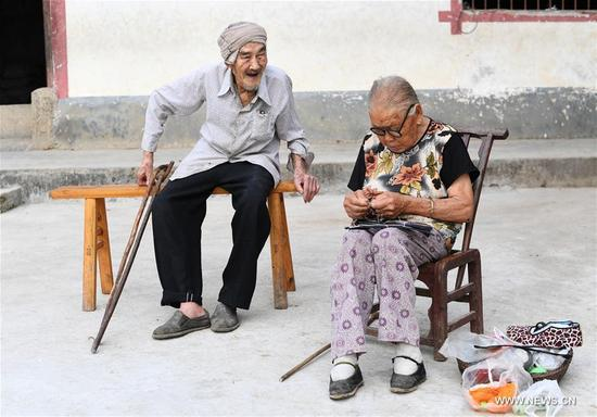 Xiang Yongshan (R) watch his wife Wu Xi'an making a shoe in Zaojiao village of Fengping township, Fengjie County, southwest China's Chongqing Municipality, Aug. 23, 2017. The 100-year-old Xiang and 101-year-old Wu has been married for 81 years. (Xinhua/Wang Quanchao)