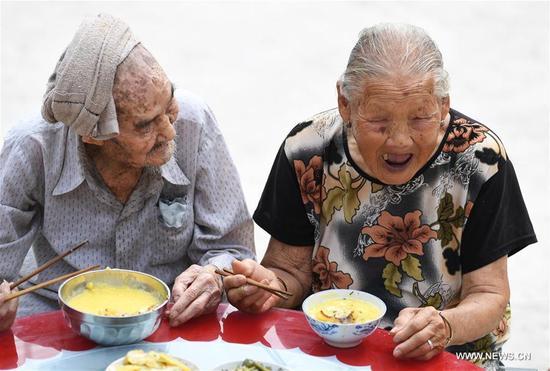 Xiang Yongshan (L) amuses his wife Wu Xi'an during their meal in Zaojiao village of Fengping township, Fengjie County, southwest China's Chongqing Municipality, Aug. 23, 2017. The 100-year-old Xiang and 101-year-old Wu has been married for 81 years. (Xinhua/Wang Quanchao)