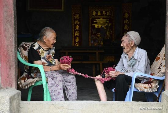 Xiang Yongshan (R) and his wife Wu Xi'an sit at the doorway and hold their love token, the bronze bell, in Zaojiao village of Fengping township, Fengjie County, southwest China's Chongqing Municipality, Aug. 23, 2017. 100-year-old Xiang and 101-year-old Wu has been married for 81 years. (Xinhua/Wang Quanchao)
