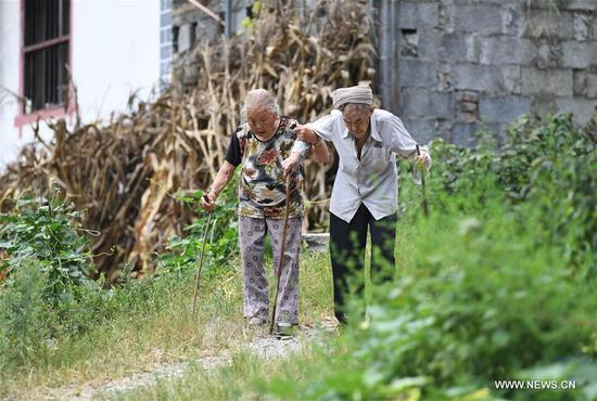 Xiang Yongshan (R) and his wife Wu Xi'an hold each other while taking a walk near their home in Zaojiao village of Fengping township, Fengjie County, southwest China's Chongqing Municipality, Aug. 23, 2017. The 100-year-old Xiang and 101-year-old Wu has been married for 81 years. (Xinhua/Wang Quanchao)