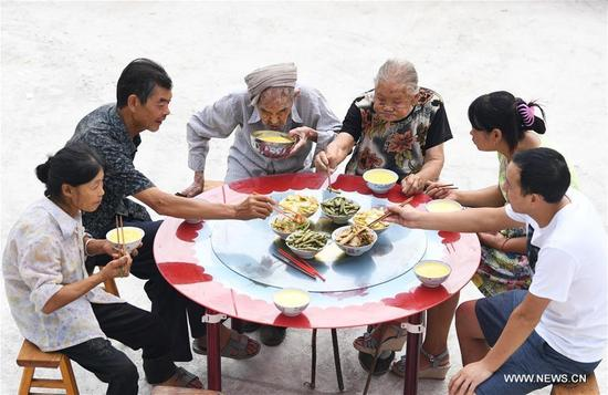Xiang Yongshan (3rd L) and his wife Wu Xi'an (3rd R) have meal with family members in Zaojiao village of Fengping township, Fengjie County, southwest China's Chongqing Municipality, Aug. 23, 2017. The 100-year-old Xiang and 101-year-old Wu has been married for 81 years. (Xinhua/Wang Quanchao)