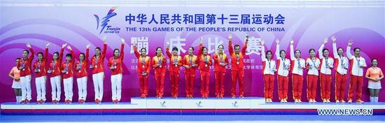 Gold medalists Guangdong trampoline team (C), silver medalists Zhejiang trampoline team (L) and bronze medalists Fujian trampoline team pose during the awarding ceremony after the trampoline women team final at the 13th Chinese National Games in north China's Tianjin Municipality, Aug. 29, 2017. (Xinhua/Lian Zhen)