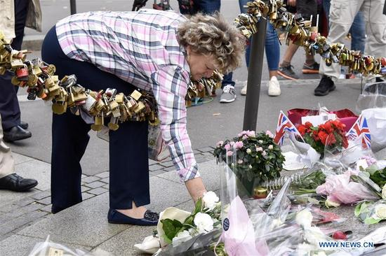 A woman places a bouquet of flowers to commemorate the Princess Diana in Paris, France on Aug. 31, 2017. People commemorated the 20th anniversary of the tragic death of Princess Diana here on Thursday. Princess Diana died in a car crash in a Parisian underpass on Aug. 31, 1997, at the age of 36. (Xinhua/Chen Yichen)