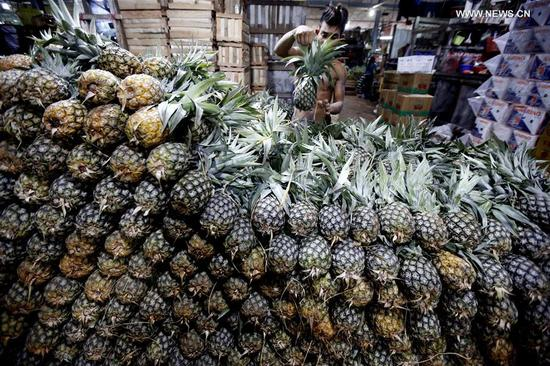 A worker arranges pineapples at the Thiri Mingalar wholesale market in Yangon, Myanmar, Sept. 6, 2017. About 95 percent of Myanmar's fruit export has gone to China during the current fiscal year, making the country Myanmar's main agricultural export market, official media reported Tuesday. (Xinhua/U Aung)
