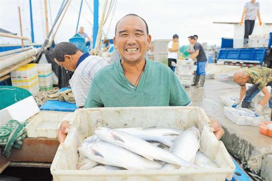 A fisherman shows off the fish caught from the East China Sea near Luchao Port. — Huang Riyue
