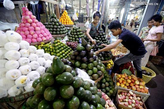 A worker selects fruit for customer at the Thiri Mingalar wholesale market in Yangon, Myanmar, Sept. 6, 2017. About 95 percent of Myanmar's fruit export has gone to China during the current fiscal year, making the country Myanmar's main agricultural export market, official media reported Tuesday. (Xinhua/U Aung)