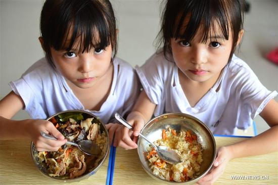 Twin girls Liu Yuting (R) and Liu Yuyao take free lunch at the No. 4 Primary School in Jianhe County of Miao and Dong Autonomous Prefecture of Qiandongnan, southwest China's Guizhou Province, Sept. 6, 2017. Free lunch project has improved diets of rural students in Guizhou since 2012. The nutritious lunches helped address malnutrition among students in remote and poor areas. (Xinhua/Yang Wenbin)