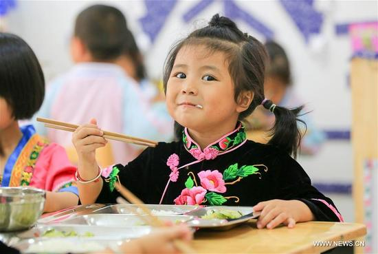 Pan Chengyue, a 4-year-old girl of Miao ethnic group, takes free lunch at the Kaihuai Community No. 13 Kindergarten, which was newly built for children relocated from poverty-stricken areas, in Kaili City, Miao and Dong Autonomous Prefecture of Qiandongnan, southwest China's Guizhou Province, Sept. 6, 2017. Nutrition program has benefited preschool children in rural area of Kaili since spring this year, with free breakfast and lunch offered to children at rural kindergartens and kindergartens for children relocated from poverty-stricken areas. (Xinhua/Wu Jibin)